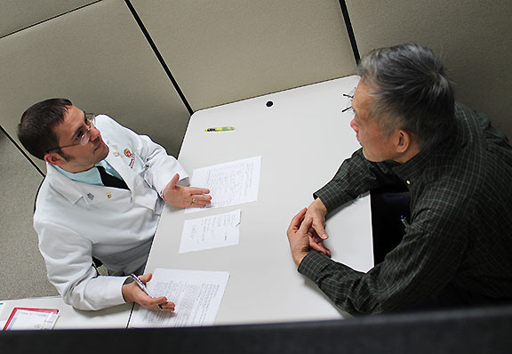 Andrew Berti (left) works with a practice patient in Communications lab.