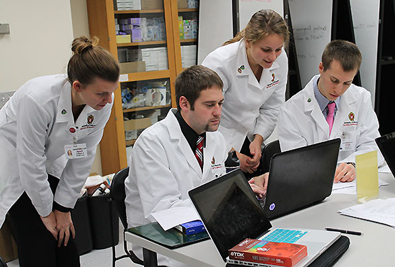 Pharmacy students discuss treatment options for a patient case in Pharmacotherapy lab.