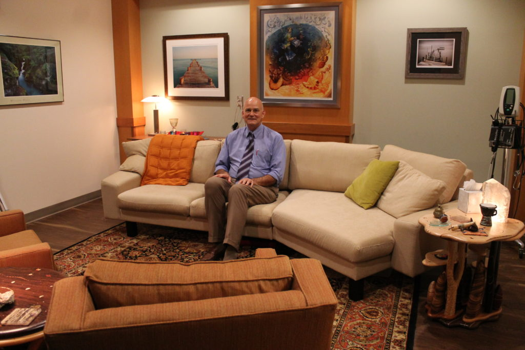 Paul Hutson sitting in the clinical therapy room, which is furnished like a living room.