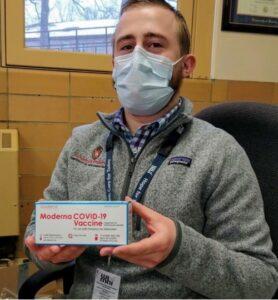 Aaron Klysen holding COVID-19 vaccine