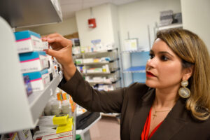 Melissa Ortega taking medication from a shelf