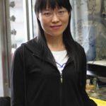 Dr. Xiao-Na Wang standing by a fume hood