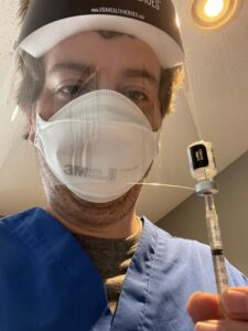 Nick Batinich in PPE, holding a vial of vaccine.
