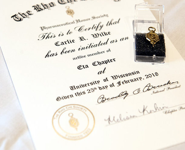 Close-up shot of Carlie Wile's Rho Chi initiate certificate and key.