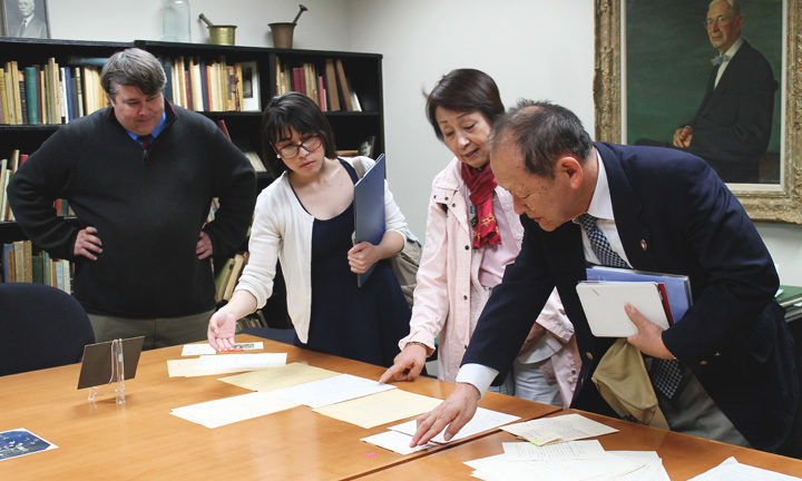 Left-right: Greg Bond, Assistant Director, American Institute of the History of Pharmacy, looks on as Kenia Elena Avendano-Garro, UW-Madison graduate student and translator, Mrs. Inoue, and Mr. Sartoru Inoue (far right), review historical documents.