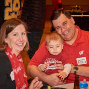 An alumni with their family and child at a School of Pharmacy tailgate party.