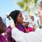 A volunteer helping children understand how to use an inhaler.