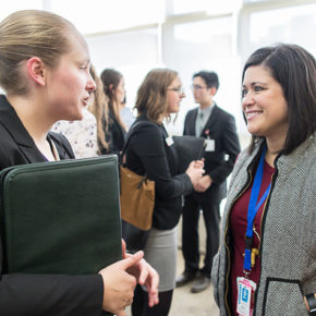 Maria Wopat (PharmD '10) (right) speaking with a student during the School of Pharmacy's 2019 Career Fair.
