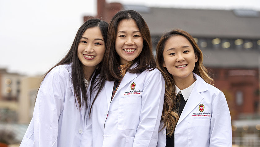 Three PharmD students outside of Memorial Union after the White Coat ceremony.