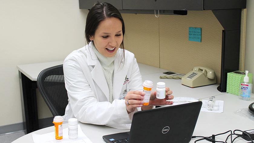 Taylor Hauser holding prescription bottles up to a webcam.