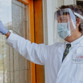 Lance Moran, dressed in PPE, knocking on a patient's door.
