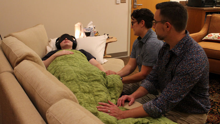 Health practitioners assist a patient during a psilocybin treatment session