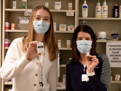 Anna Lattos and Kate Cain holding vials of COVID vaccine