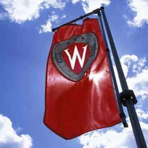 "A ""W"" crest banner flies on Bascom Hill against blue sky and puffy clouds during spring. ©UW-Madison University Communications Photo by: Jeff Miller"