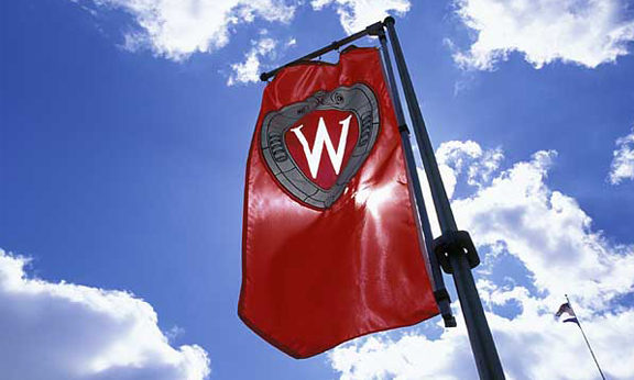 """A """"W"""" crest banner flies on Bascom Hill against blue sky and puffy clouds during spring. ©UW-Madison University Communications Photo by: Jeff Miller"""