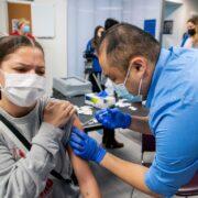 PharmD student Mark Moua gives the Covid vaccine. Photo by Paul L. Newby II
