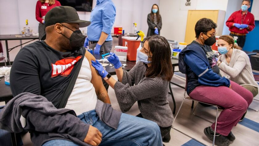 PharmD students Janvi Shah (left) and Kathryn Freitag (right) give the COVID-19 vaccine to a couple at the vaccine clinic held at the McKenzie Family Boys & Girls Club in Sun Prairie. Photo by Paul L. Newby II