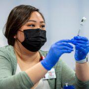 PharmD student Phanary Xiong prepares the Covid vaccine. Photo by Paul L. Newby II