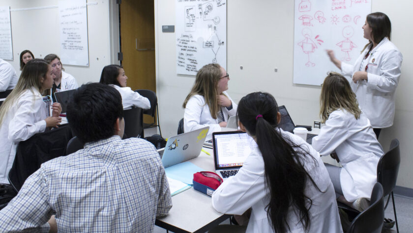 A group of PharmD students in white coats collaborating at a table in front of a white board.