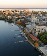 The Lake Mendota shoreline is pictured in an aerial view of the University of Wisconsin-Madison campus looking toward the downtown Madison skyline during an autumn sunset on Oct. 5, 2011. Major campus facilities pictured from center to right include Memorial Library, Armory and Gymnasium (Red Gym), the Memorial Union Terrace and Helen C. White Hall. On the horizon is the Wisconsin State Capitol and Lake Monona. The photograph was made from a helicopter looking southeast. (Photo by Jeff Miller/UW-Madison)