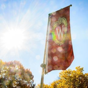 Sunlight shines through an iconic W crest banner on Bascom Hill at UW-Madison.