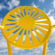 A yellow Memorial Union Terrace chair is pictured against a sunny blue sky at UW-Madison.. The chair is known for its iconic sunburst design. (Photo by Jeff Miller/UW-Madison)