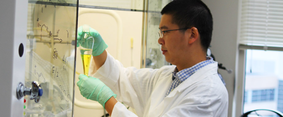 MCC scientist Zhi-Xiong Ma inspects a vial in the chemical hood.