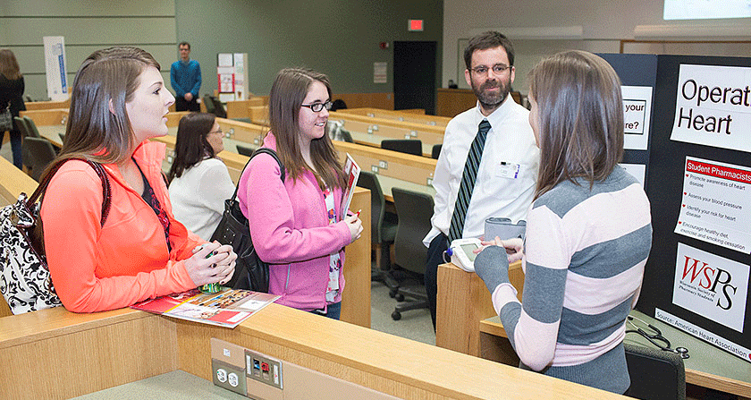 Open House attendees chat with a pharmacy student about the various student organizations.