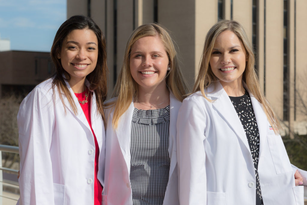 PharmD students Haley Stafford (left), Alexandra Edinger (center), and Elizabeth Janet (right) pose outdoors following the 2018 White Coat Ceremony.
