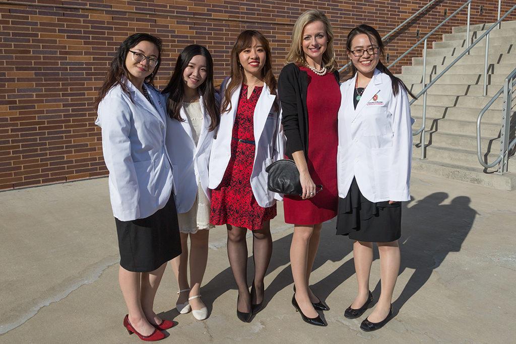 Pharmacy students Chunxi Zhou, Jiaying Zhang, Mengqi Zhang, and Trinh Trinh pose with Professor Beth Martin following the 2018 Pharmacy White Coat Ceremony.
