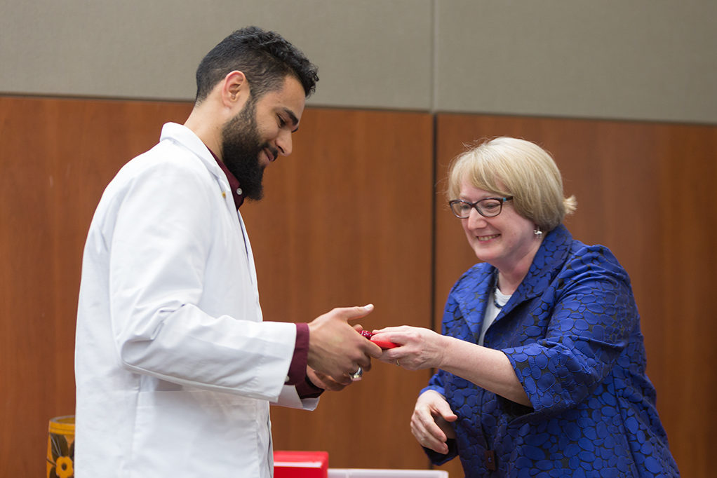 Associate Professor Karen Kopacek awards the pin to the students.