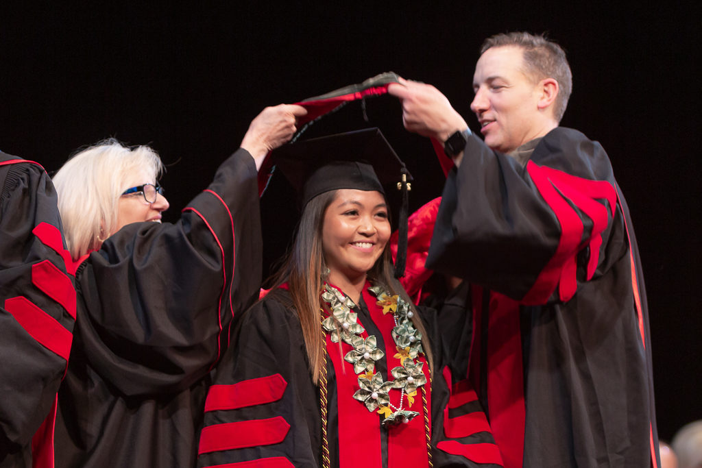 A student is awarded the hood from the school faculty.