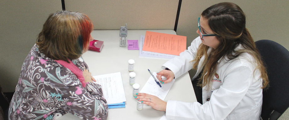 A third-year pharmacy student counsels a practice patient in communications lab.
