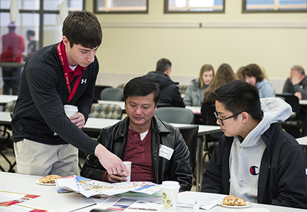 Student Ambassador and second-year PharmD student Joshua Becco shows Oak Creek high school student (right) Ethan Nguyen and his father, Tuan Nguyen some places on the UW campus map during the School of Pharmacy Preview Day at Rennebohm Hall on Saturday, April 14, 2018.